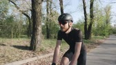 주기 : Happy joyful cyclist smiling while riding bicycle in park. Cyclist wearing black outfit helmet and sunglasses. Cycling concept.