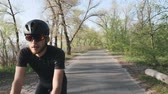 주기 : Relaxed athletic fit cyclist riding a bicycle in the park. Front follow shot. Bearded cyclist wearing black outfit easy ride on bike. Slow motion