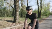 주기 : Happy joyful cyclist smiling while riding bicycle in park. Cyclist wearing black outfit helmet and sunglasses. Cycling concept. Slow motion
