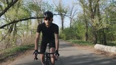 주기 : Focused confident cyclist pedaling out of the saddle. Front follow shot. Professional cyclist wearing black outfit on bicycle. Slow motion