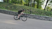주기 : Bike rider fast descending down the hill in the park. Cyclist wearing helmet on curvy downhill road. Slow motion 무비클립