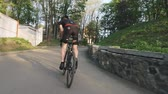racefiets : Cyclist with strong legs pedaling out of the saddle climbing the hill. Cycling training concept. Follow shot. Slow motion Stockvideo