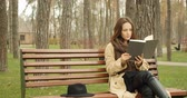 literatura : Young cute girl sitting in park on a bench and reading a book with black hat placed near her. Reading concept