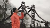 refrescar : Caucasian brunette woman drinks energy drink from bottle outdoor. Female athlete in orange bright jacket drinking water from bottle in park. Sport and running concept Vídeos