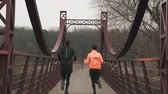 Backside view of young sportive couple running across bridge in parkland. Woman and man athletes in bright sportswear jogging outdoor. Male and female run on bridge across river