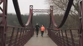 Motivated young couple training in park. Sportive young woman and man are jogging across pedestrian bridge. Female and male athletes running together. Sports and run concept Stock Footage