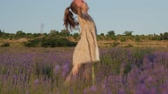 lavanda : cute little girl playfully dances among beautiful lavender field at sunset Stock Footage