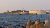 sevastopol : time lapse shooting view of the white lighthouse on the other side of the coastline at sunset boats and ships, Stock Footage