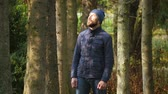 Happy young guy enjoying sunlight in city park. bearded man standing in an outerwear and knitted hat outdoor Stok Video