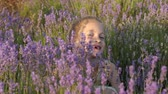 embraced : close-up face cute little girl sitting in lavender flowers and inhaling fragrance of flowers warm summer sunset. concept rest and relaxation
