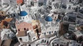 Top aerial view of Three Blue Domes church in Oia town on Santorini island, Greece Stok Video