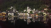 à beira do lago : Aerial view of boat arrive in Hallstatt village over calm Hallstatter See at sunny summer morning, in Salzkammergut, Upper Austria. Stock Footage