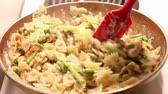 A red spatula mixes and stirs a delicious looking pasta dish in a skillet