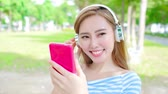 campus : woman smile happily and use phone listen music in the park