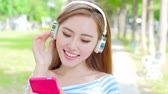 university : woman smile happily and use phone listen music in the park