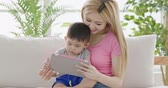 mommy use digital tablet with son on sofa at home