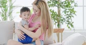 sarılma : mommy hug her son and sit on sofa at home Stok Video