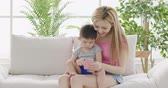 mommy use phone with son on sofa at home Stock Footage