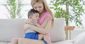 mommy hug her son and sit on sofa at home Stock Footage