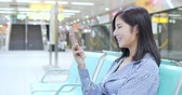 mrt : business woman use phone and sit on chair in train station Stock Footage