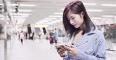 mrt : business woman play mobile game in train station