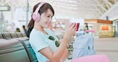 espera : woman sit wear headphone and use phone watch video in the station