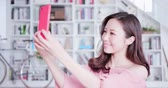estante : Young woman take a selfie by smart phone at home Vídeos