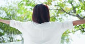 протяжение : Back view of young woman feel carefree and take a deep breath at nature outdoor