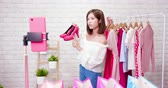magasin vetement : beauty female fashion vlogger show shoes to cellphone and smiling selling it online live streaming