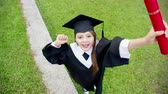diploma : Girl gratuate lift arm happily with diploma holding in hand