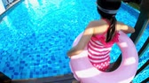 надувной : cute girl play with floating ring and jump into swimming pool Стоковые видеозаписи