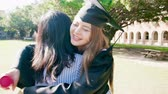 diploma : Girl gratuate give friend a hug happily in the campus