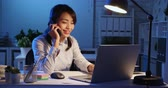 říci : asian woman overtime work and speak on the phone in the office