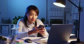sekreter : asian woman overtime work and talk to ai audio assistant in the office Stok Video