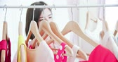 karar vermek : young woman choosing clothes on a rack at home Stok Video