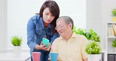 aposentar : Young daughter teach elder father use mobile at home Stock Footage