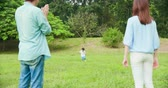 fű : Little boy try to run in the park and parents are very happy