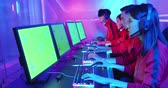Team of asian teenage cyber sport gamers play in multiplayer PC video game on eSport tournament with green screen