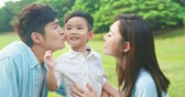 slow motion of young asian parents kiss their kid happily in the park