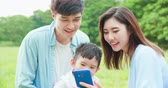 Young asian parent and kid look smartphone happily at park