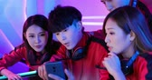 Team of asian teenage cyber sport gamers discuss about their strategy before play mobile game by smartphone on eSport tournament