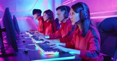 Team of asian teenage cyber sport gamers wear headsets on and play in multiplayer PC video game on eSport tournament Wideo