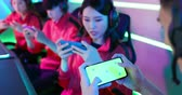 Team of asian teenage cyber sport gamers play mobile game by 5g full display smartphone on eSport tournament with green screen Wideo