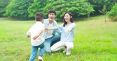 slow motion of asian parents play with kid outdoor and boy run into their hug