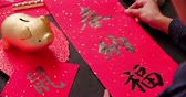 zodiaque chinois : asian people write calligraphy on couplet to celebrate chinese new year with word meaning luck