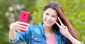 park : young asian girl take selfie with her smart phone