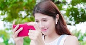ecouter la musique : young asian woman watch video and wear wireless earbuds with her smart phone in the park Vidéos Libres De Droits