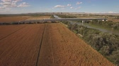 em linha reta : Fast train enters bridge near cultivated corn field and river