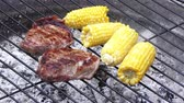 steaks with corn cooking outdoors on fire Stok Video