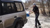 nagyon : man tourist pours SUV water from a bucket that would wash